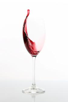 グラスから注がれた赤ワイン。飲み物用食器 Premium写真
