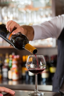 Red wine pouring in glass at bar