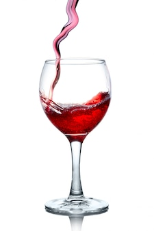 Red wine pouring in glass isolated