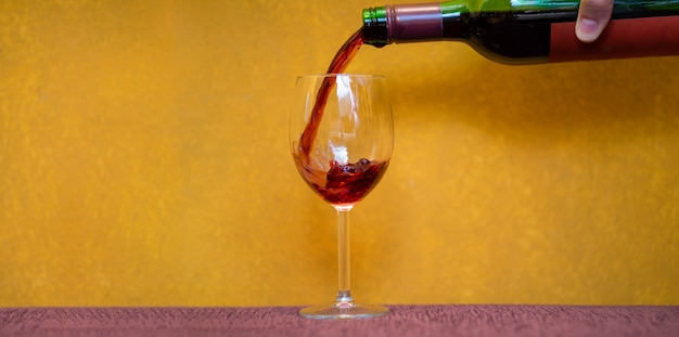 Red wine pouring in a glass on yellow background with copy space