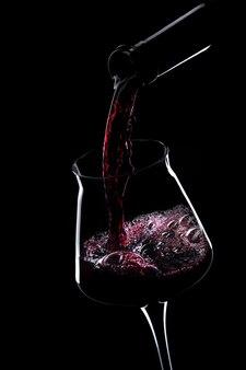 Красное вино наливает в стакан из бутылки.