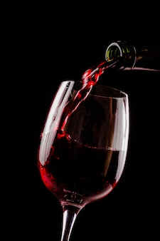 黒の背景にボトルからワイングラスに注ぐ赤ワイン。コピースペース付きのワインリストデザインメニュー。アルコール飲料カードの背景。