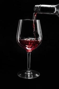 Красное вино наливается в бокал для вина