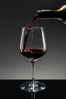 Vino rosso che si versa in un bicchiere da vino