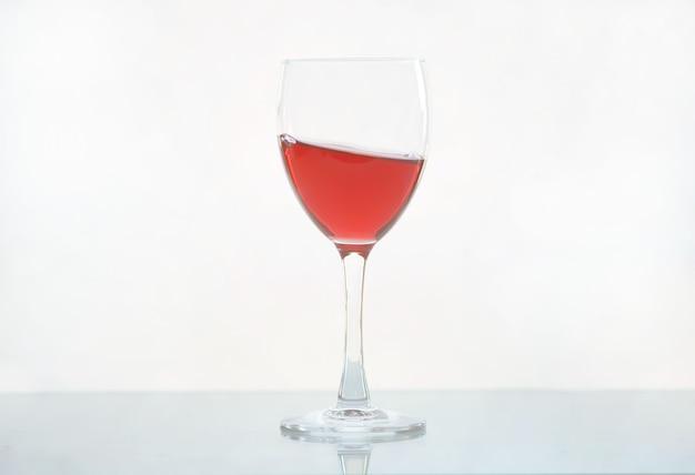 흰색 유리 배경에 유리 잔에 레드 와인 붓는 동작. 적포도주 한 방울이나 맛있는 붉은 액체로 튀기십시오. 와인 튀김. 유리는 광택 있는 흰색 표면에 서 있고 흰색으로 격리되어 있습니다.