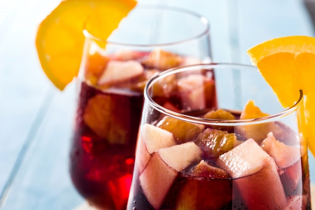 Red wine sangria in glass on blue wooden table close up