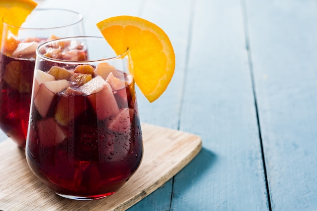 Red wine sangria in glass on blue wooden table, copy space