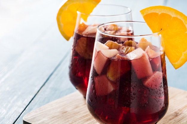 Red wine sangria in glass on blue wooden table