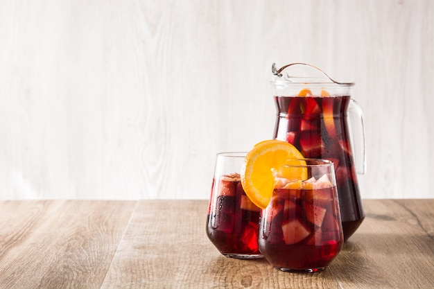 Red wine sangria in glass on wooden table copy space