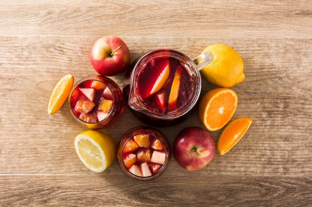Red wine sangria in glass on wooden table, top view