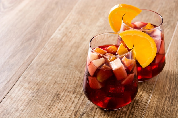Red wine sangria in glass on wooden table