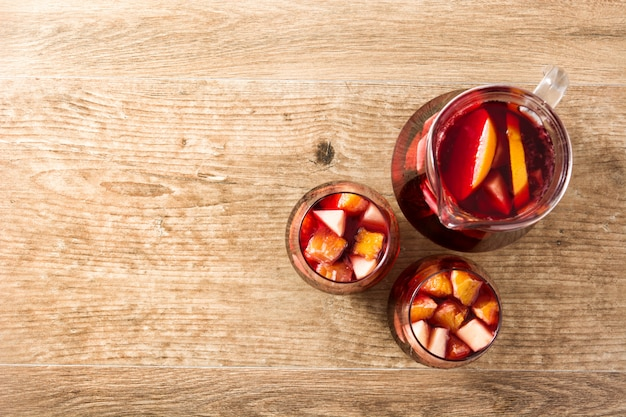 Red wine sangria in glasses on wooden table