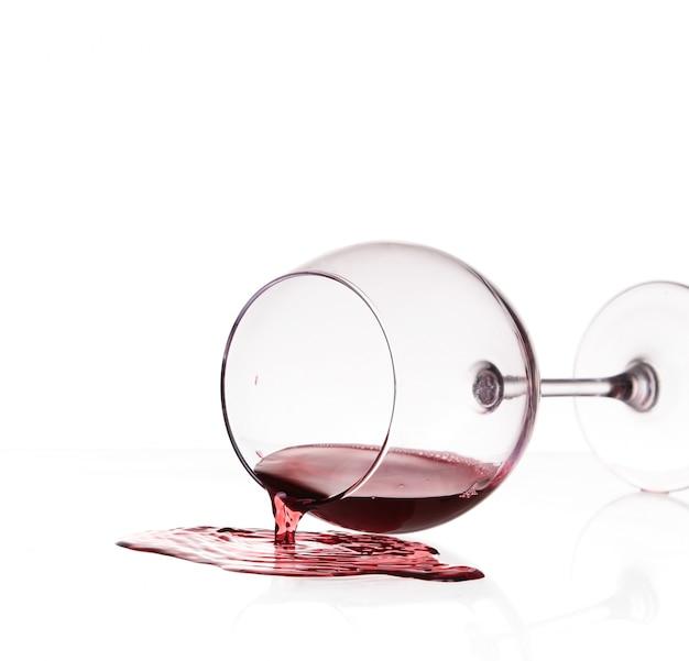 Красное вино пролилось из стекла на белом фоне