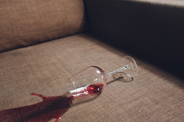 Red wine spilled on a grey couch sofa.