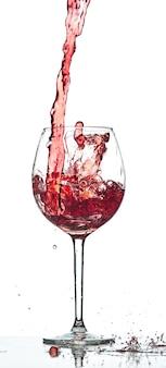 Red wine splash over white background at studio