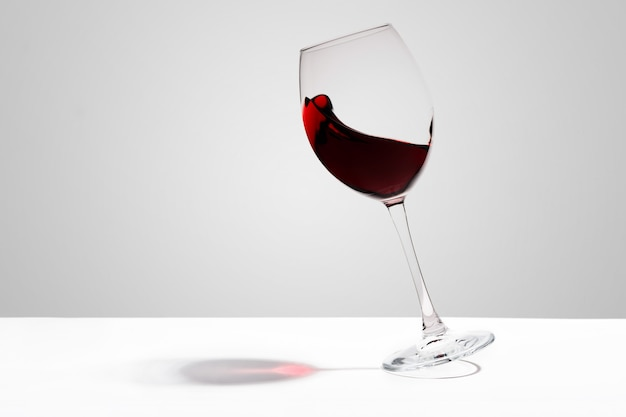 Red wine splashes in a glass on white