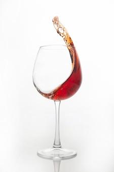 레드 와인은 밝은 배경에 유리에서 튀었습니다. 알코올 중독과 중독. 휴가를위한 음료