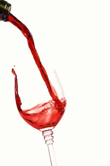 Red wine splashing into the glass isolated