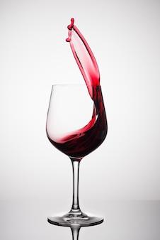 Красное вино брызгает из стакана