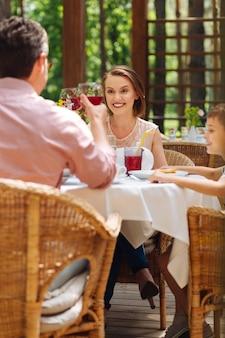 赤ワイン。彼らの小さなかわいい息子の誕生日を祝っている間赤ワインを飲む2人の晴れやかな両親 Premium写真