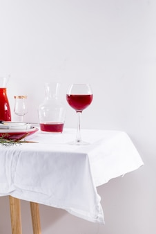 Red wine in a wineglass, decanter and table setting with shadows
