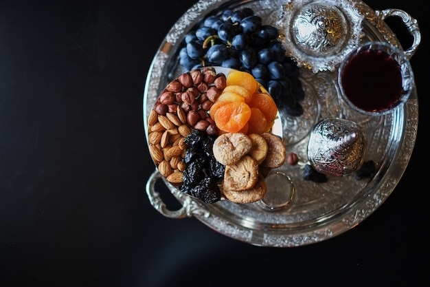 Red wine, wineglass with walnuts, grapes and figs on dark background