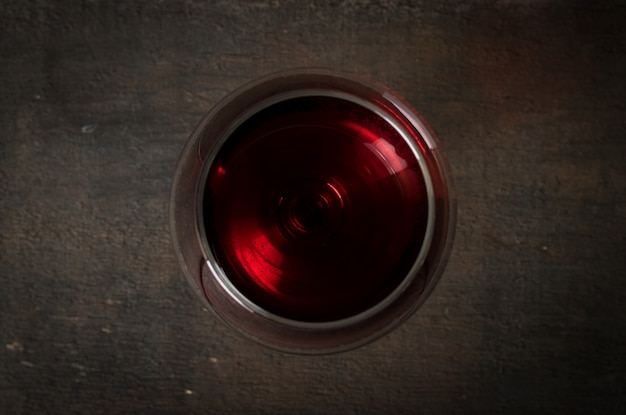 Red wine in wineglass on wood