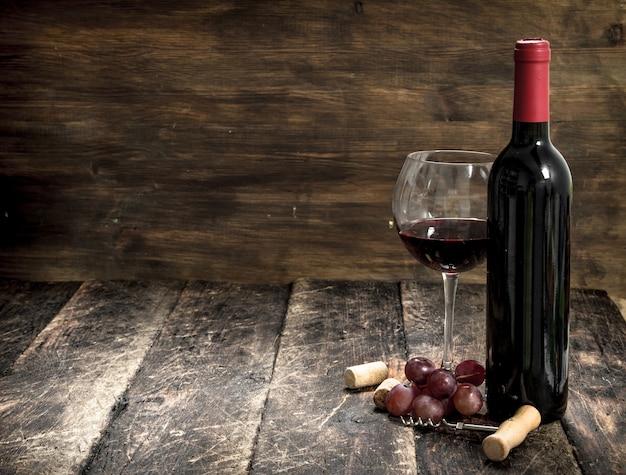 葡萄の枝と栓抜きのある赤ワイン。木製の背景に。