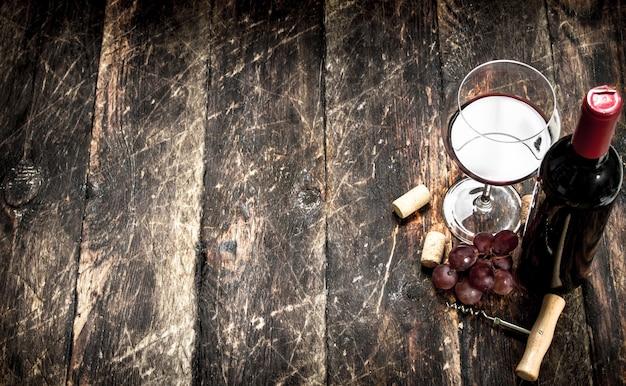 ブドウの枝と木製のテーブルに栓抜きが付いた赤ワイン。