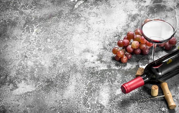 素朴なテーブルにコルク栓抜きをした赤ワイン。