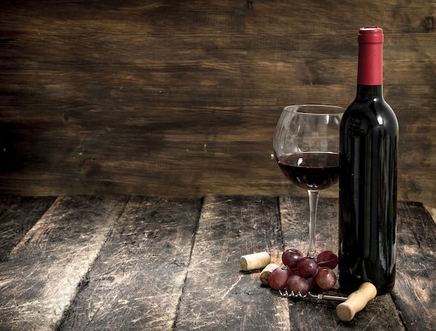 Red wine with a branch of grapes and a corkscrew. on a wooden background.