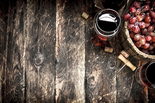 Red wine with a bucket of grapes on wooden table.