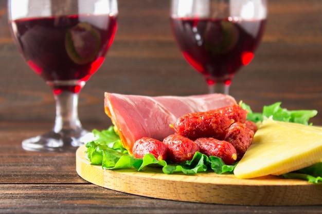 Красное вино с ассортиментом колбас на заднем плане