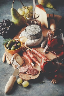 Red wine with charcuterie assortment on the stone background