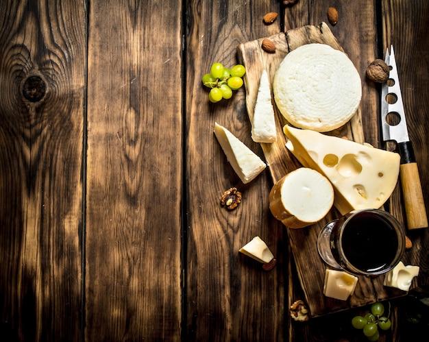 치즈와 견과류 덩어리와 레드 와인. 나무 테이블에.
