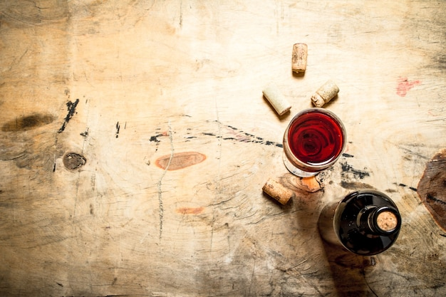 Red wine with corks. on wooden background.