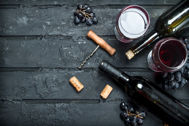 Red wine with corkscrew on black rustic table.