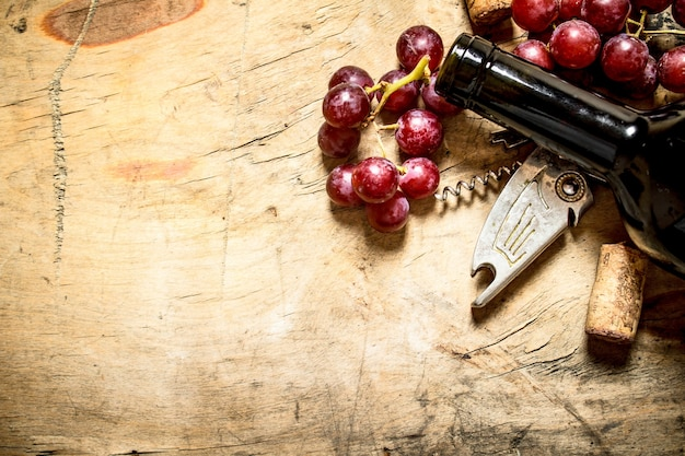 Red wine with a corkscrew, grapes and corks on wooden background