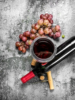 Red wine with a corkscrew. on a rustic background.