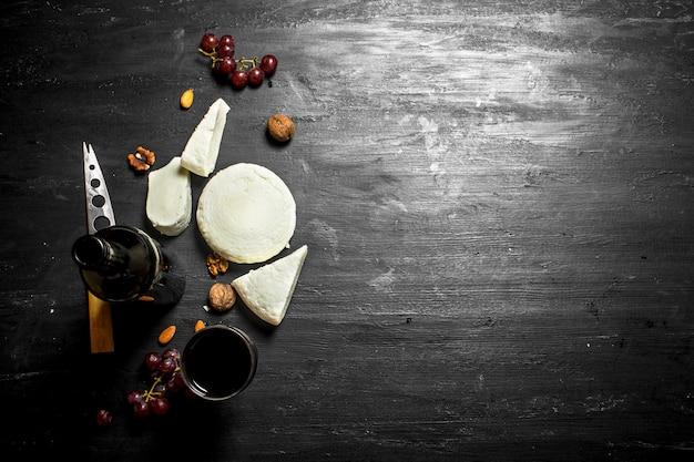 신선한 양 치즈와 포도와 레드 와인. 검은 나무 배경에