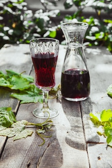 Red wine with grape leaves in jug and glass on wooden and plants table, high angle view.