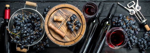 Red wine with grapes and an old barrel.