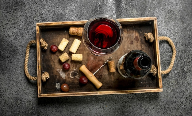 Red wine on a wooden tray. on a rustic background.