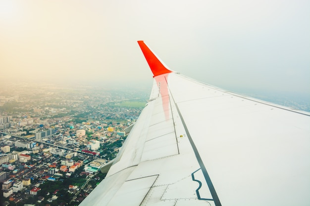 Red wing of the aircraft view from airplane window seat during take off and flying above city landscape