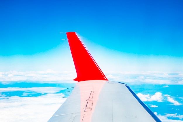 The red wing of the plane on the background of a bright blue sky, the concept-we fly to travel