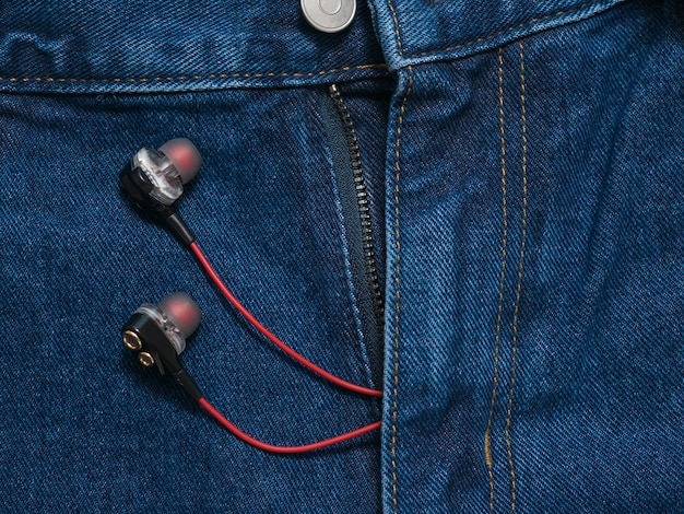 Red with black headphones sticking out of his pants blue jeans. fashionable youth style.