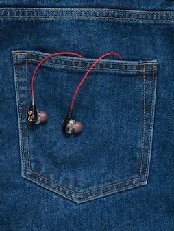 청바지 주머니에서 튀어 나온 검은 헤드폰이 달린 빨간색. 유행 청소년 스타일.
