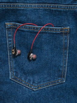 Red with black headphones sticking out of the pocket of blue jeans. fashionable youth style.