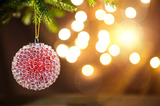 Красный с ледяными прыщами рождественский бал на живой ветке ели с золотыми огнями гирлянд в расфокусировке. новый год, рождество, праздник фон, боке, копия пространства