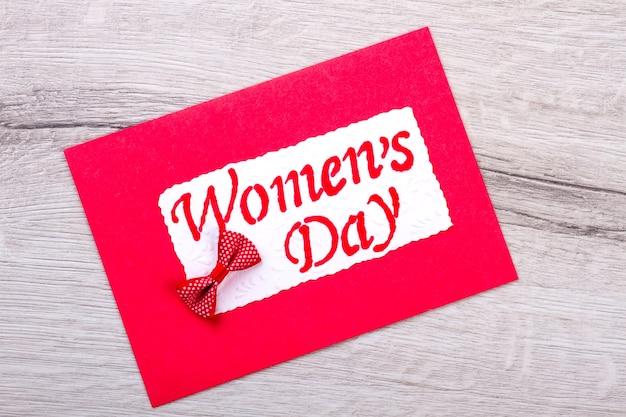 赤い女性の日のグリーティングカード。カードと弓の組み合わせ。プレゼントで女性を祝福します。創造性の実践。